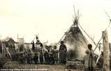 A group of children near a teepee with a church in the background, [Alberta].