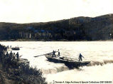 One boat traveling down river rapids. The boat is being steered by men with large oars, [Alberta].