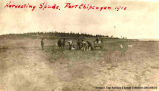 A group of people working in a field with one small wagon beside them, Fort Chippewyan. A note on...
