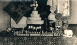 Decorated wedding cake with ornate cutlery and other utensils. All items on a table with...