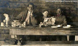 Three men at a wooden table with utensils and reading material, [Alberta]. Note at bottom of  the...