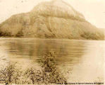 Large hill viewed from across a body of water, [Alberta].