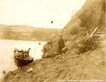 One boat landed on a steep shore. There are men in the boat and men standing on the shore,...