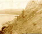 Several men standing on a steep rocky shore. There are boats in the distance traveling down a body...