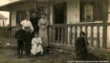 A family outside a house in front of the porch, Fort Chippewyan. Note on the back reads:...