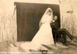 Portrait of a bride and groom, the bride is standing and groom is seated. A dark blanket or sheet...