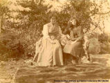 Portrait of two women. They are in a field with tress as a background. Both women are seated on...