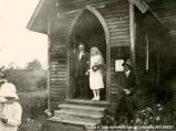 A portrait of a bride and a groom standing in an open church door. He is wearing a suit and she a...