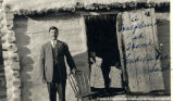 One man standing outside a house leaning on a chair. Two children are standing in the open...