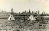 Two teepees in a field with a fence in the background, Fort Simpson. Note on the front reads:...