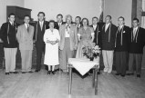 Group of men and women standing (with white dress shirts, narrow neck ties and floral headpieces)